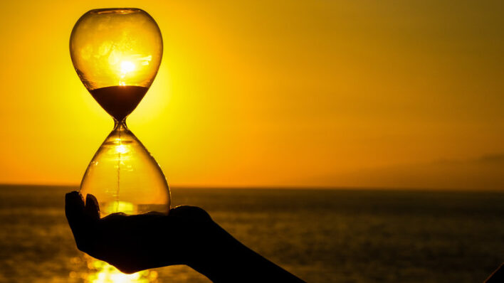 woman holding an hourglass over the sun showing time