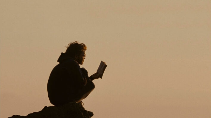 man reading book at sunset how to read more often