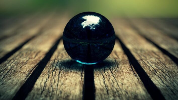 blue marble ball in focus on a wooden floor nature
