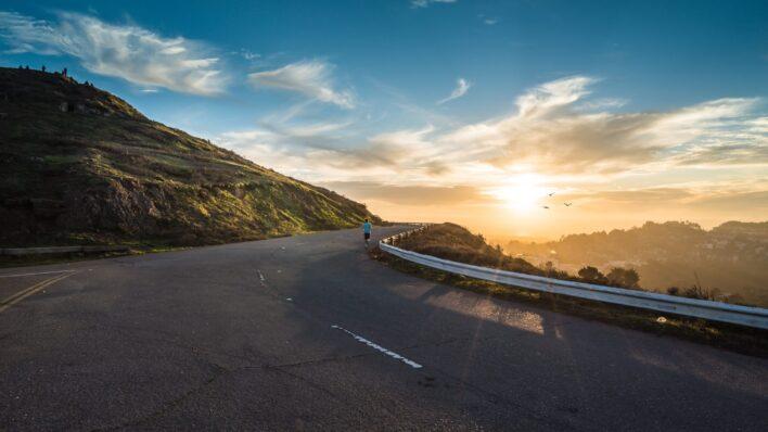 develop self-discipline man running the road sunset