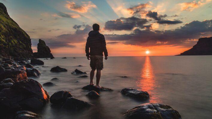 man-standing-rock-looking-sunset