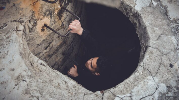 woman-climbing-out-of-hole