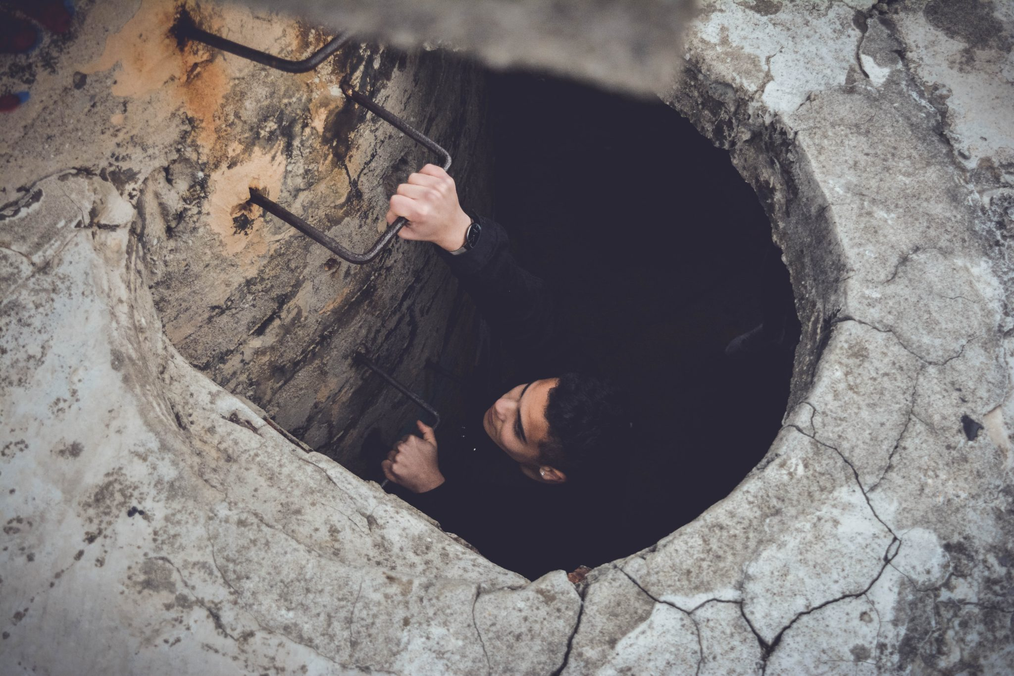 Woman Climbing Out Of Hole