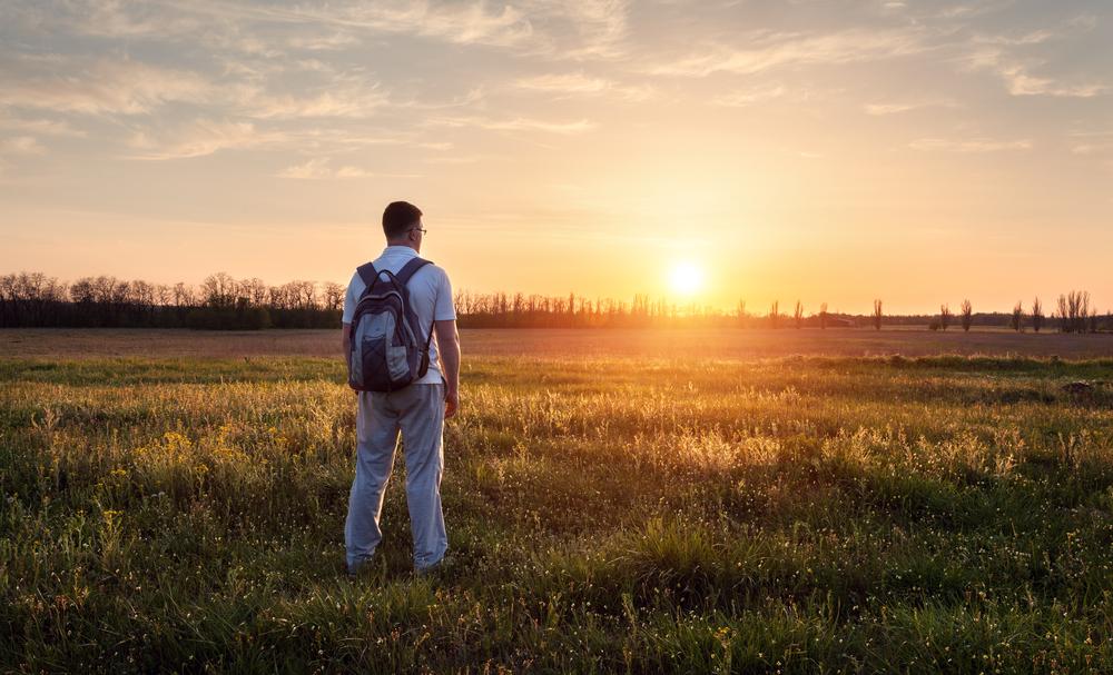 man-standing-field-contemplating-priorities
