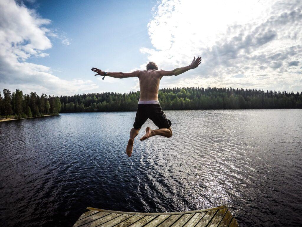 man-jumping-lake
