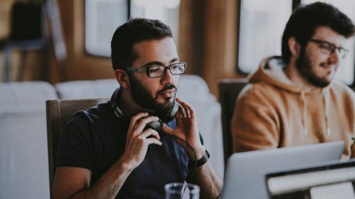 man-taking-off-headphones-while-working-laptop