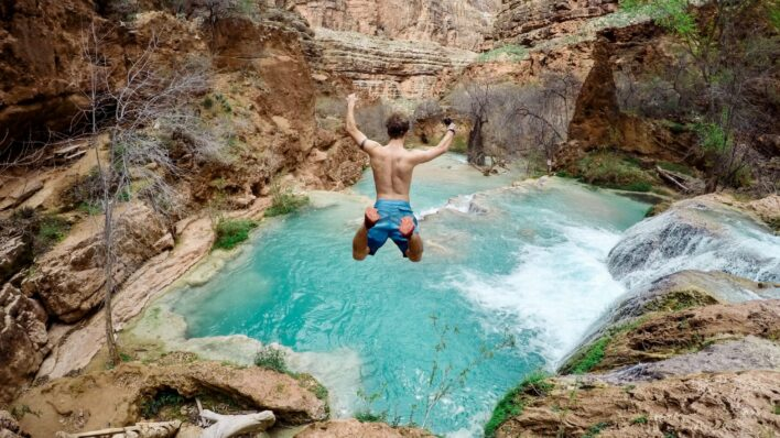 man-taking-leap-faith-jumping-off-cliff