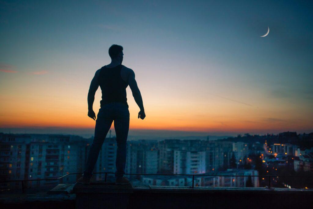 fit-man-standing-roof-overlooking-city
