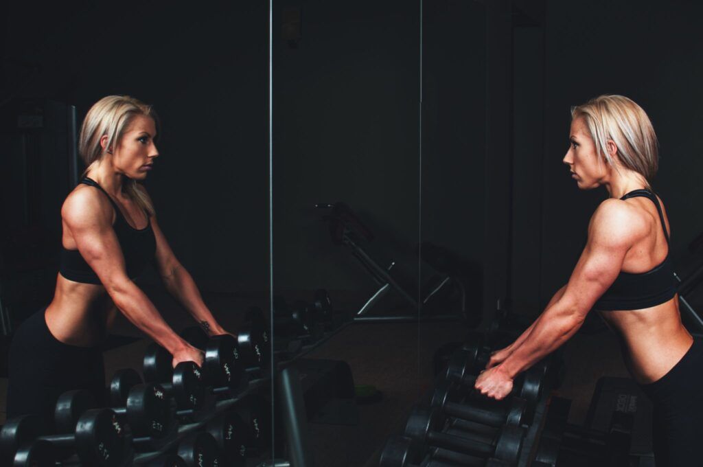woman-lifting-weights-looking-mirror