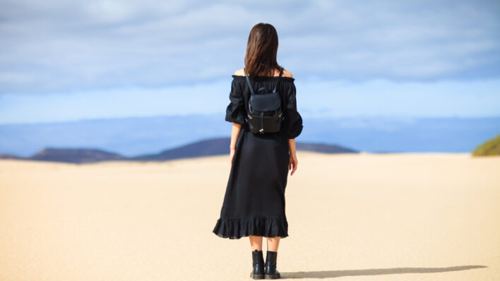 woman-black-dress-looking-desert