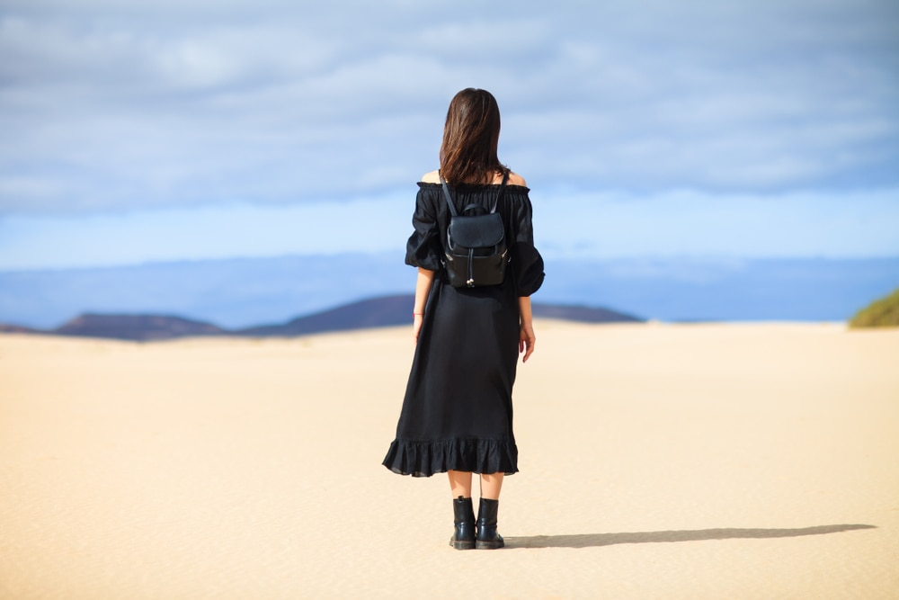 woman-black-dress-looking-desert