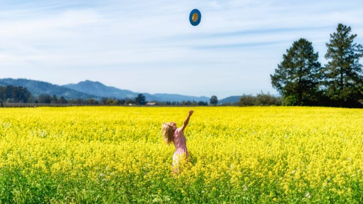 woman-throwing-hat-yellow-field