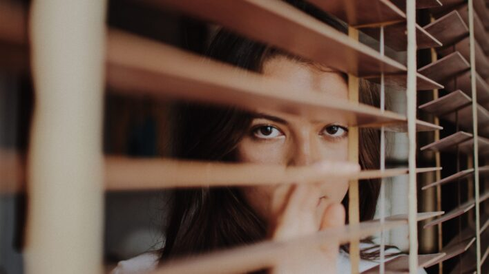 shy-woman-looking-through-blinds