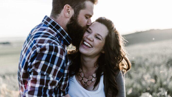 man-kissing-woman-cheek-making-smile