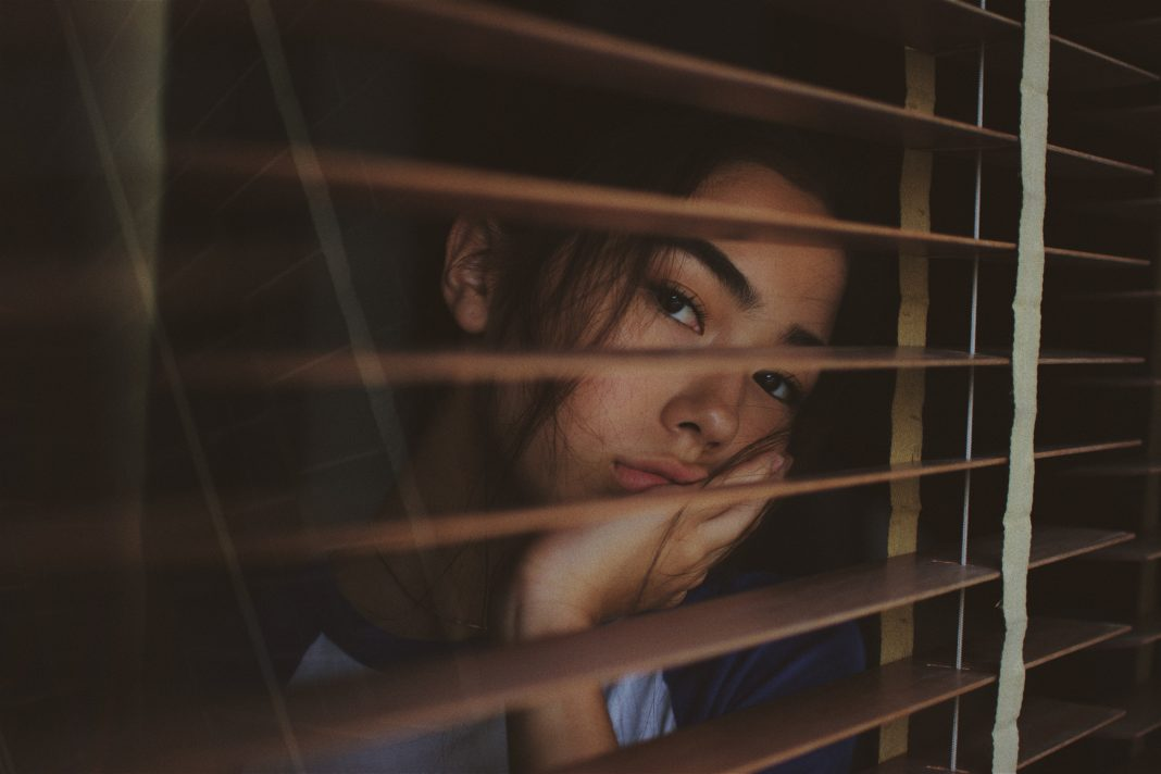 Woman-looking-through-shutters